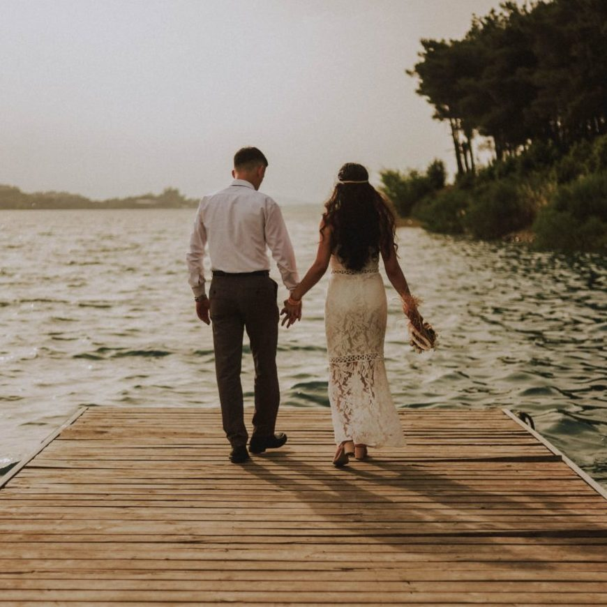 Image: Happy couple holding hands walking on peir