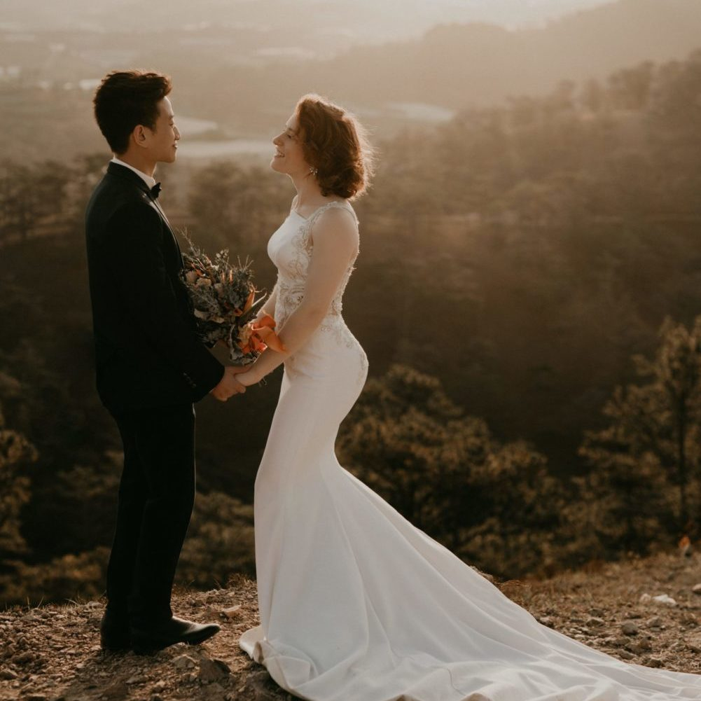 Image: happy bride and groom posing in front of canyon